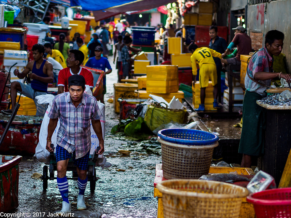 23 NOVEMBER 2017 - YANGON, MYANMAR: A laborer delivers ice in the San Pya Fish Market. San Pya Fish Market is one of the largest fish markets in Yangon. It's a 24 hour market, but busiest early in the morning. Most of the fish in the market is wild caught but aquaculture is expanding in Myanmar and more farmed fresh water fish is being sold now than in the past.    PHOTO BY JACK KURTZ