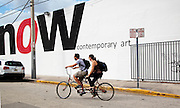 A couple rides a bicycle built for two past the NOW art gallery sign in Miami's Wynwood arts district.