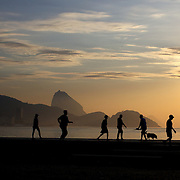 Early morning walkers at sunrise on Copacabana beach, Rio de Janeiro,  Brazil. 9th July 2010. Photo Tim Clayton..The beaches of Rio de Janeiro, provide the ultimate playground for locals and tourists alike. Beach activity is in abundance as beach volley ball, football and a hybrid of the two, foot volley, are played day and night along the length and breadth of Rio's beaches. .Volleyball nets and football posts stretch along the cities coastline and are a hive of activity particularly at it's most famous beaches Copacabana and Ipanema. .The warm waters of the Atlantic Ocean provide the ideal conditions for a variety of water sports. Walkways along the edge of the beaches along with exercise stations and cycleways encourage sporting activity, even an outdoor gym is available at the Parque Do Arpoador overlooking the ocean. .On Sunday's the main roads along the beaches of Copacabana, Leblon and Ipanema are closed to traffic bringing out thousands of people of all ages to walk, run, jog, ride, skateboard and cycle more than 10 km of beachside roadway. .This sports mad city is about to become a worldwide sporting focus as they play host to the world's biggest sporting events with Brazil hosting the next Fifa World Cup in 2014 and Rio de Janeiro hosting the Olympic Games in 2016..