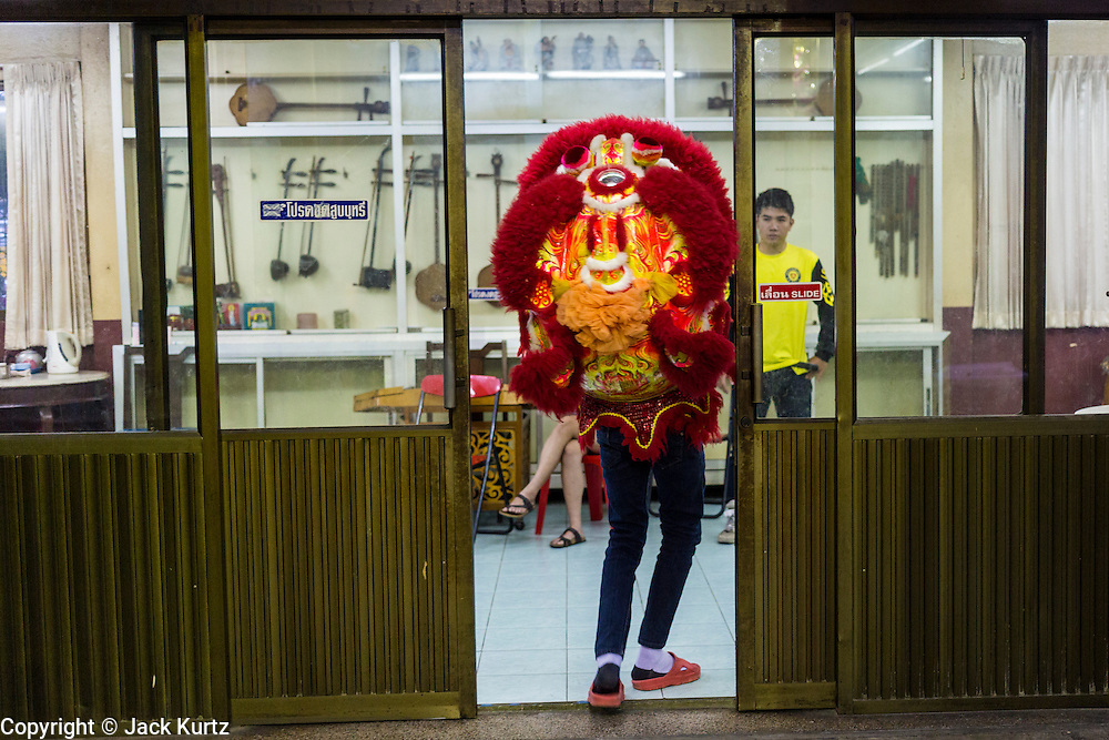 09 FEBRUARY 2014 - HAT YAI, SONGKHLA, THAILAND: A lion dancer carries his head into an office during Lunar New Year in the Tong Sia Siang Tueng temple in Hat Yai. Hat Yai was originally settled by Chinese immigrants and still has a large ethnic Chinese population. Chinese holidays, especially Lunar New Year (Tet) and the Vegetarian Festival are important citywide holidays.     PHOTO BY JACK KURTZ