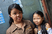 "Mar. 21, 2009 -- BANGKOK, THAILAND: Thai girls in an alley in the Monk's Bowl Village. The Monk's Bowl Village on Soi Ban Baat in Bangkok is the only surviving one of what were originally three artisan's communities established by Thai King Rama I for the purpose of handcrafting ""baat"" the ceremonial bowls used by monks as they collect their morning alms. Most monks now use cheaper factory made bowls and the old tradition is dying out. Only six or seven families on Soi Ban Baat still make the bowls by hand. Most of the bowls are now sold to tourists who find their way to hidden alleys in old Bangkok. The small family workshops are only a part of the ""Monk's Bowl Village."" It is also a thriving residential community of narrow alleyways and sidewalks.     Photo by Jack Kurtz"