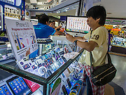 21 SEPTEMBER 2013 - BANGKOK, THAILAND:  A man looks at an iPhone in an electronics shop in MBK in Bangkok. Customers around the world lined up Friday to pick up Apple's new flagship iPhone 5s and its lower cost, more colorful brother, the iPhone 5c. The phones went on sale in the US and select countries beyond the US on Friday. The iPhone 5s and iPhone 5c will not be officially released in Thailand until late 2013 but the phones are available through the unofficial grey market in MBK, a huge shopping complex in Bangkok with dozens of small electronics shops. Early purchasers in Thailand pay a premium for the new iPhones, the top of the line iPhone 5s with 64 gigabytes of memory is about 38,500Baht, more than $1,200 (US).     PHOTO BY JACK KURTZ