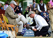 © Licensed to London News Pictures. 16/09/2012. Goodwood, UK . A man has his shoes shined. People enjoy the atmosphere at the 2012 Goodwood Revival. The event recreates the glorious days of motor racing and participants are encouraged to dress in period dress. Photo credit : Stephen Simpson/LNP