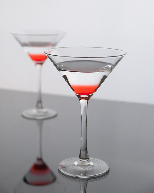 two pink martini drinks on a reflective surface