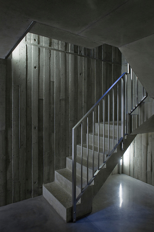concrete staircase inside a modern concrete house with metal handrail.