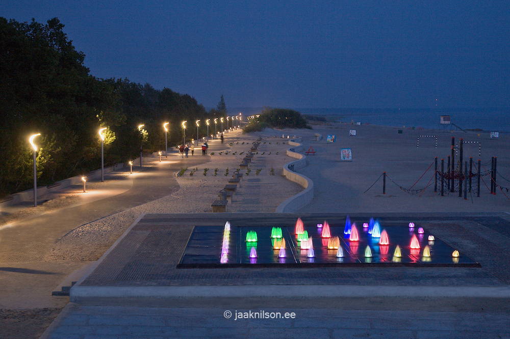 Lighted beach promenade with fountains in Pärnu, Estonia. Seaside resort at night.