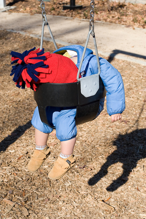 A toddler dressed in winter clothing asleep face first in a swing.