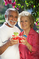 Portrait of senior couple with drinks outdoors