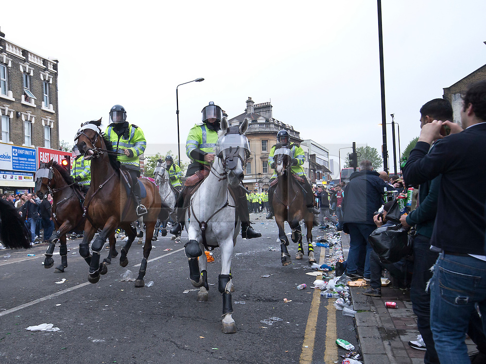 © Licensed to London News Pictures. 10/05/2016. LONDON, UK. Mounted Police charge down the Barking Rd in an attempt to disperse West Ham United fans who were celebrating the clubs final game at the Boleyn Ground against Manchester United. Photo credit: LNP