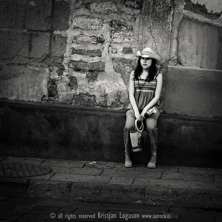 Stylish Young Woman resting on a house wall in the streets of Oaxaca, Mexico