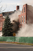 A portion of the front wall of the former Holy Childhood school building in Harbor Springs collapses when demolition equipment pulled down a large section of the buildings roof.