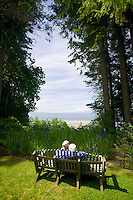 A senior couple share a quiet moment while strolling through the grounds at Milner gardens & woodland, a seaside garden set in natural coastal Douglas-fir woodland in Qualicum Beach. Vancouver Island, British Columbia, Canada.