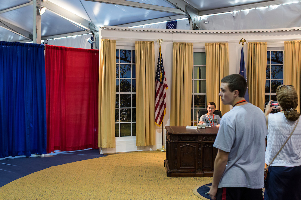 Guests at the American Presidential Experience exhibit pose for pictures in a pretend Oval Office on Sunday, September 2, 2012 in Charlotte, NC.