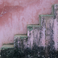 Asia, Vietnam, Hue, Mildewed stairs along pastel colored wall at Thien Mu Pagoda in late afternoon
