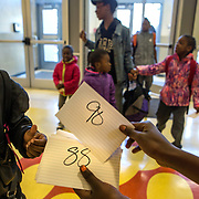 WASHINGTON, DC - APR 24:  Students receive a numbered index card as they enter Simon Elementary School in Washington, DC, April 24, 2014. The index cards become a ticket for a daily raffle of items like pencils, snacks, or even backpacks, held each day in the cafeteria during breakfast. DC has enormous truancy rates, even among young children. In the last year or two, the school system has made a big push to improve attendance. Simon Elementary is seen as a model, introducing incentives and games that are tied to attendance and meant to get kids excited about coming to school; systems to ensure that parents get a call home whenever their kids are absent; weekly attendance meetings to talk about kids who are missing too much school; and a partnership with a community based organization that can make home visits and connect families with services. (Photo by Evelyn Hockstein/For The Washington Post)