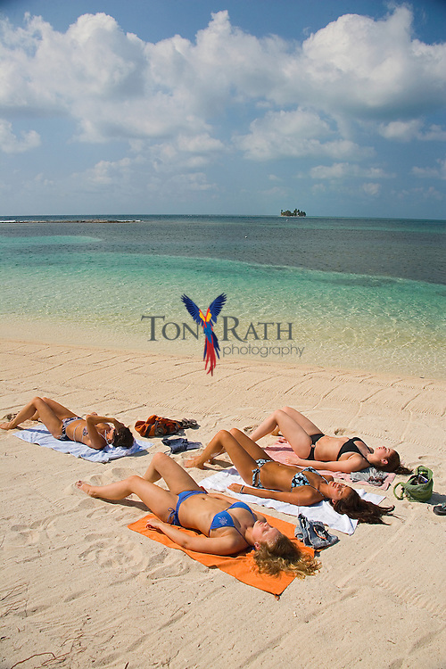 Young women sunbathing on south beach at South Water Caye, Belize