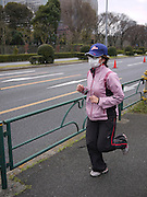 Japan, Tokyo woman jogs with facial surgical mask