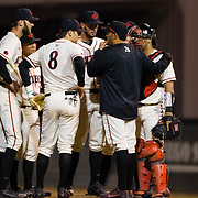 24 February 2018: The San Diego State Aztec baseball team competes in day two of the Tony Gwynn legacy tournament against #4 Arkansas. San Diego State Aztecs pitching coach Sam Peraza (26) talks with the infield with the bases loaded in the top of the seventh. The Aztecs dropped a close game to the Razorbacks 4-2. <br /> More game action at sdsuaztecphotos.com