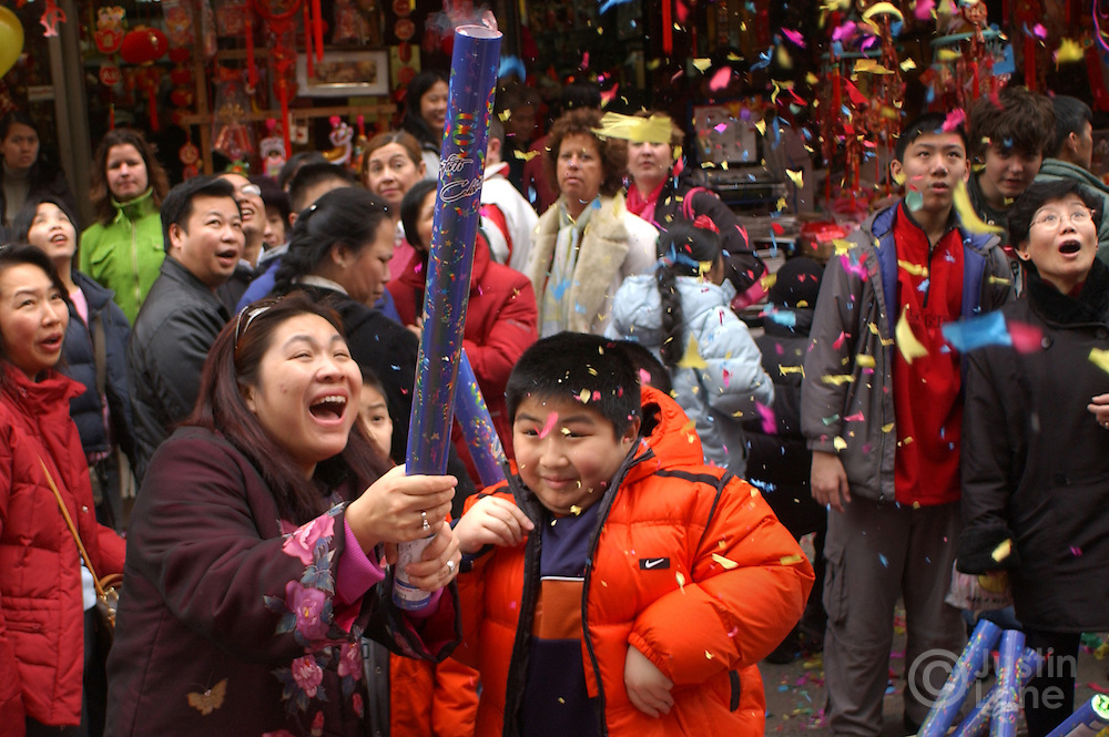 Hong Mo (L) and her son Daniel, 9 1/2, (R) react after setting off confetti during Chinese New Year celebrations in Chinatown in New York Wednesday 9 February 2005.