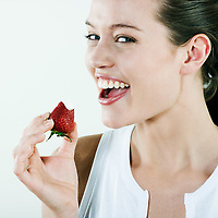 studio portrait on isolated background of a young beautiful caucasian woman eating a strawberry