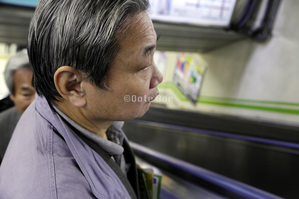 senior Asian male person on escalator Japan