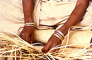 Close-up of a woman of the Cholanaicken tribe,one of the most primitive indigenous communities of India and still living in caves,weaving a fibre mat in front of the family cave.