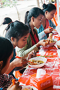 Young Khmer women eating fermented rice noodles topped with 'curry' (num banh chok), Preaha Da/Siem Reap