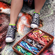 Street chalk artist Stacey Williams-Ng sports Converse All Stars as she sits beside her basket of colorful drawing supplies at Bastille Days in Milwaukee. Photo by Jennifer Rondinelli Reilly. All rights reserved. NO USE WITHOUT PERMISSION.