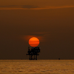 A offshore oil platform and wells are seen at sunset in the Gulf of Mexico off the coast of Louisiana, U.S., on Thursday, July 15, 2010. Photographer: Derick E. Hingle/Bloomberg
