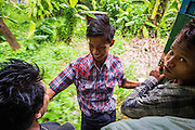 15 JUNE 2013 - YANGON, MYANMAR:  Boys sit in the door of the Yangon Circular Train. The Yangon Circular Railway is the local commuter rail network that serves the Yangon metropolitan area. Operated by Myanmar Railways, the 45.9-kilometre (28.5mi) 39-station loop system connects satellite towns and suburban areas to the city. The railway has about 200 coaches, runs 20 times and sells 100,000 to 150,000 tickets daily. The loop, which takes about three hours to complete, is a popular for tourists to see a cross section of life in Yangon. The trains from 3:45 am to 10:15 pm daily. The cost of a ticket for a distance of 15 miles is ten kyats (~nine US cents), and that for over 15 miles is twenty kyats (~18 US cents). Foreigners pay 1 USD (Kyat not accepted), regardless of the length of the journey.    PHOTO BY JACK KURTZ