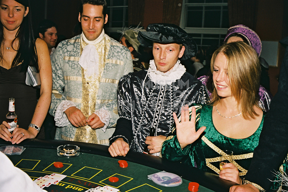 Excited punters in historical fancy dress placing bets in the Casino at Posh, Addington Palace, UK, August, 2004
