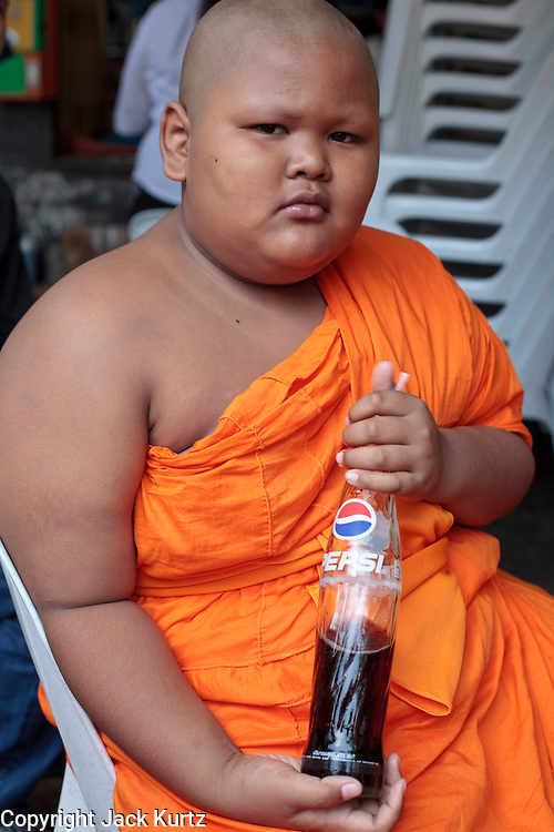 "Mar. 21, 2009 -- BANGKOK, THAILAND:  A novice monk drinks a Pepsi in the Monk's Bowl Village in Bangkok. The Monk's Bowl Village on Soi Ban Baat in Bangkok is the only surviving one of what were originally three artisan's communities established by Thai King Rama I for the purpose of handcrafting ""baat"" the ceremonial bowls used by monks as they collect their morning alms. Most monks now use cheaper factory made bowls and the old tradition is dying out. Only six or seven families on Soi Ban Baat still make the bowls by hand. Most of the bowls are now sold to tourists who find their way to hidden alleys in old Bangkok. The small family workshops are only a part of the ""Monk's Bowl Village."" It is also a thriving residential community of narrow alleyways and sidewalks.     Photo by Jack Kurtz"