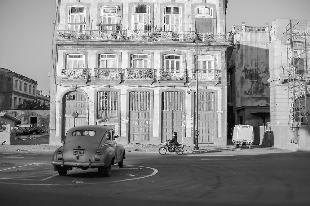 Woman rides moped scooter near docks in Havana, Cuba. Copyright 2005 Reid McNally.