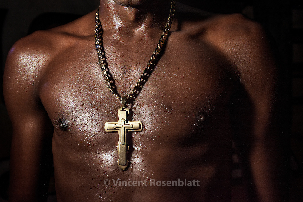 "Crucifix on a ""funkeiro's"" torso, Baile at Sítio da Boa, in São Gonçalo, Rio de Janeiro far suburb, but with a strong Funk tradition in this poor town ..The Funk carioca movement is fashion and look as well : The boys show off their muscles and naked torsos, adorned with chains and tattoos, accessories which will make the difference during the ball. Girls will look after their bikini marks, which will appear above mini-skirts or micro-shorts. Everything is worth to draw attention!"