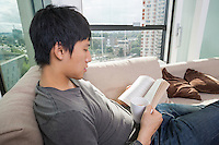Side view of mid adult man having coffee while reading book on sofa