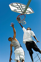 Basketball player guarding another as he shoots basketball low angle view