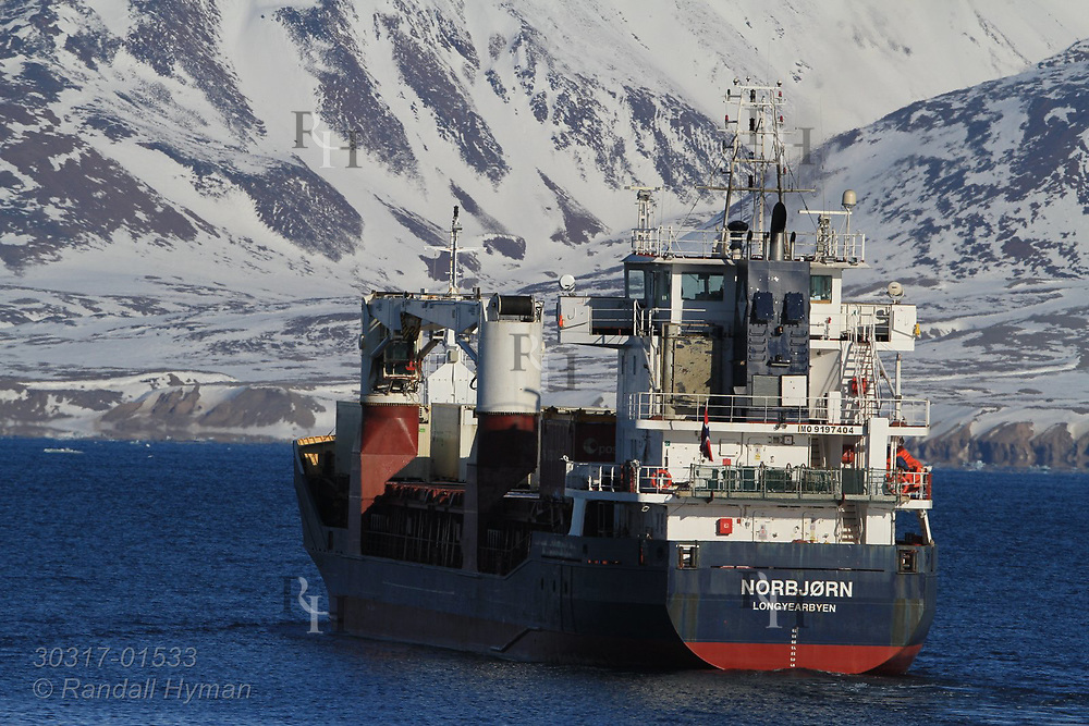Freighter and supply ship Norbjorn leaves international science village of Ny-Alesund on Spitsbergen island in Kongsfjorden; Svalbard, Norway.