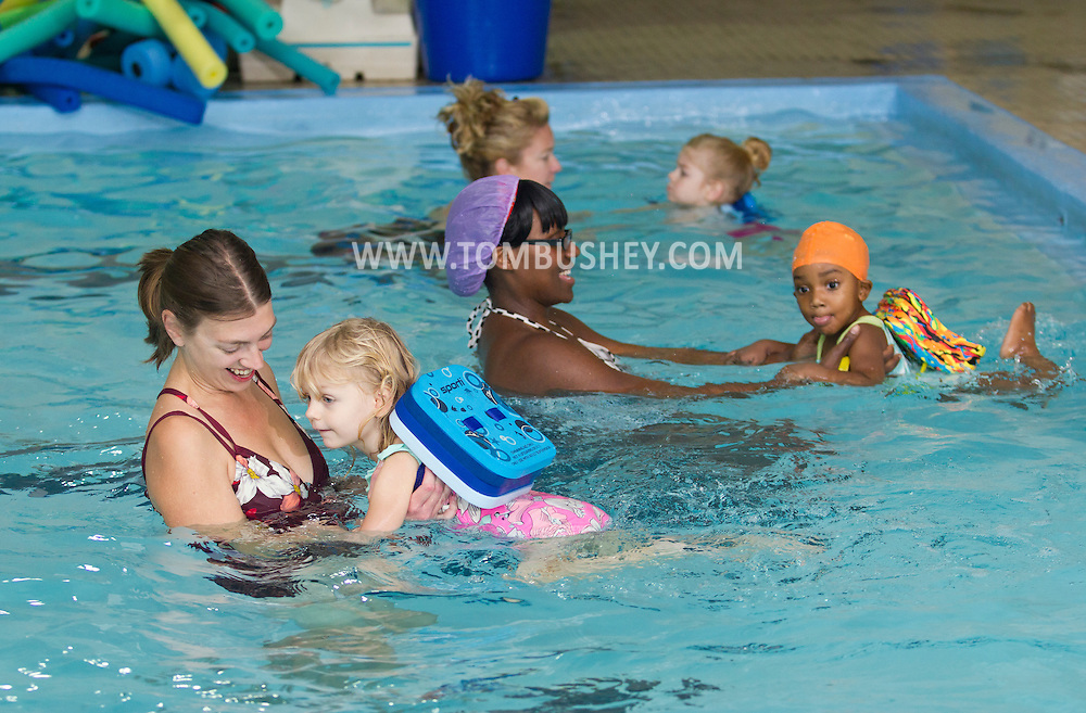 Middletown, New York - Mothers help their daughters swim during a parent and child swimming class at the YMCA of Middletown on Nov. 5, 2014.