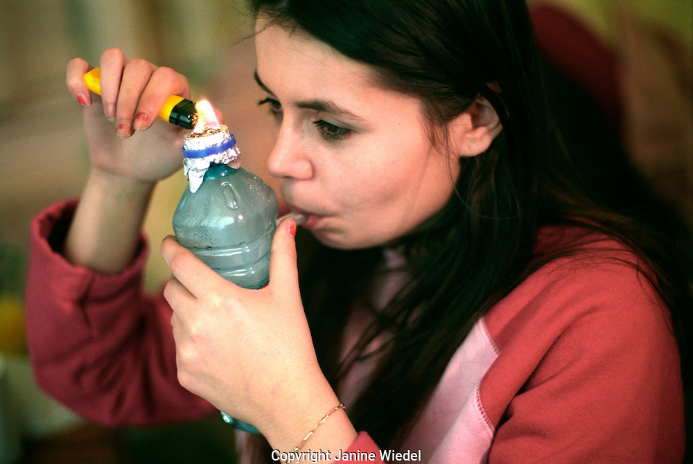 Young woman smoking crack cocaine from a home made water pipe.