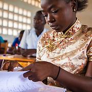LÉGENDE: Une étudiante consulte ses notes avant de passer son interrogation écrite. LIEU: CERFER, Lomé, Togo. PERSONNE(S): Etudiante (gauche) Ière année mécanique.