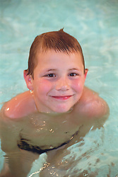 Portrait of young boy with visual impairment and hyper mobility affecting wrists; elbows and thumbs swimming in public swimming pool,