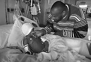 Kevin Rahman Hutchins comforts his son Quadir following surgery  to repair his scull.