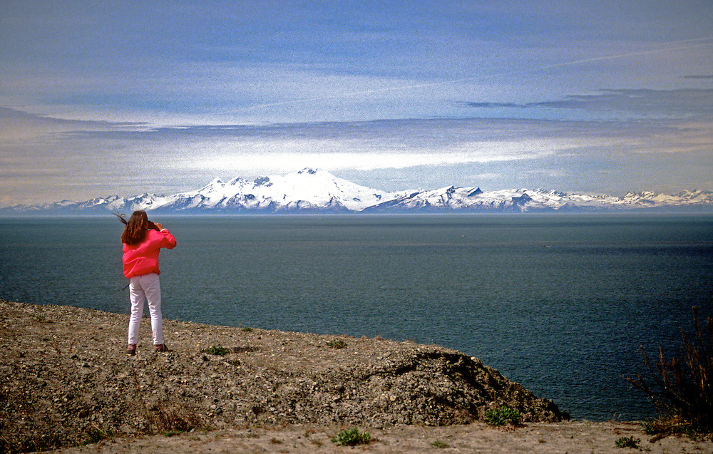 Ninilchik, AK:  A traveler photographs the scenery along the Sterling Highway drive on the west coast of the Kenai Peninsula.  The mountain in the background, across the Cook Inlet, is Redoubt Volcano in the Lake Clark National Park and Preserve.