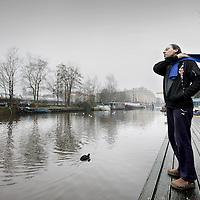 Nederland, Amsterdam , 28 februari 2011..Een bijna door woonboten verlaten gracht bij Entrepotdok..Woonbooteigenaar Rob Zijnen bekijkt vanaf de kade de lege gracht..Helemaal aan het einde ligt zijn woonboot..Foto:Jean-Pierre Jans