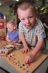 Nursery school boy and girl in classroom playing with wooden boards and coloured pegs on desk,