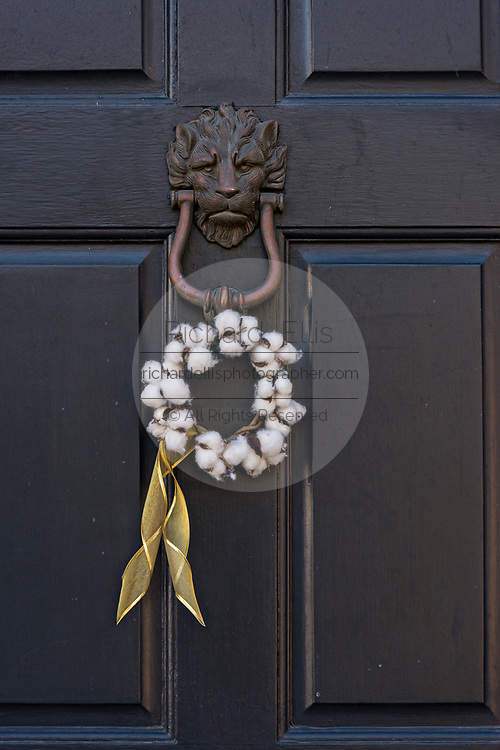 A low country style Christmas wreath made from cotton balls hangs from a historic home along Chalmers Street in Charleston, SC.
