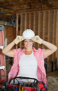Portrait of a happy young female contractor wearing hardhat at construction site