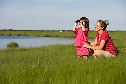 A mom and her young daughter birdwatching in the tidal estuary of Plum Island Sound.  awyer's Island, Rowley, Massachusetts.