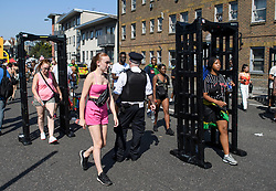 © Licensed to London News Pictures. 26/08/2019. London, UK. Carnival goers pass through knife arches, used by police to detect knives, at day two of the Notting Hill carnival. The two day event is the second largest street festival in the world after the Rio Carnival in Brazil, attracting over 1 million people to the streets of West London. Photo credit: Ben Cawthra/LNP
