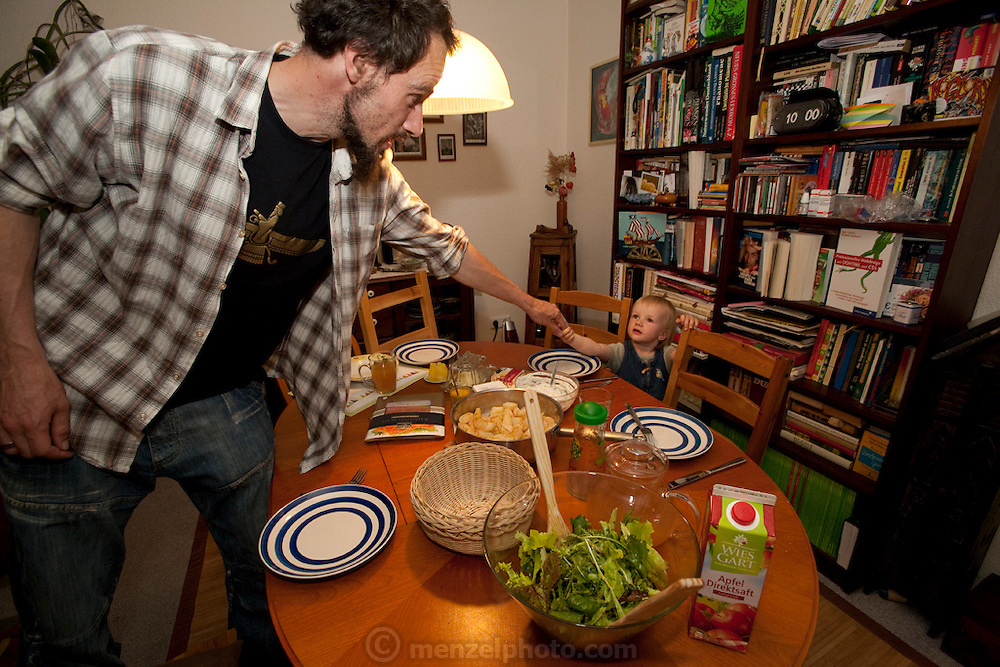 Michael Sturm family at suppertime in Hamburg, Germany, with daughter Lillith. They were photographed for the Hungry Planet: What I Eat project with a week's worth of food. Model Released.